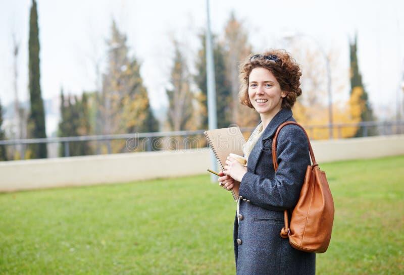 Carnet de transport et café d'étudiant roux féminin à aller photos libres de droits