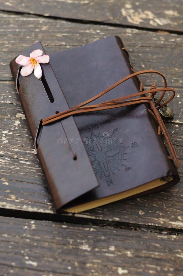 Carnet en cuir avec la fleur rose photographie stock