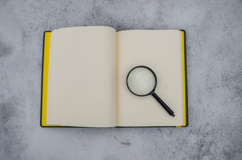 Carnet et loupe ouverts sur le fond de la neige blanche photographie stock libre de droits
