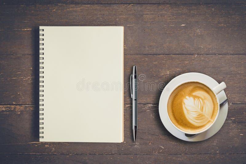 Carnet et stylo de vue supérieure avec la tasse de café sur la table en bois, vintage photos stock