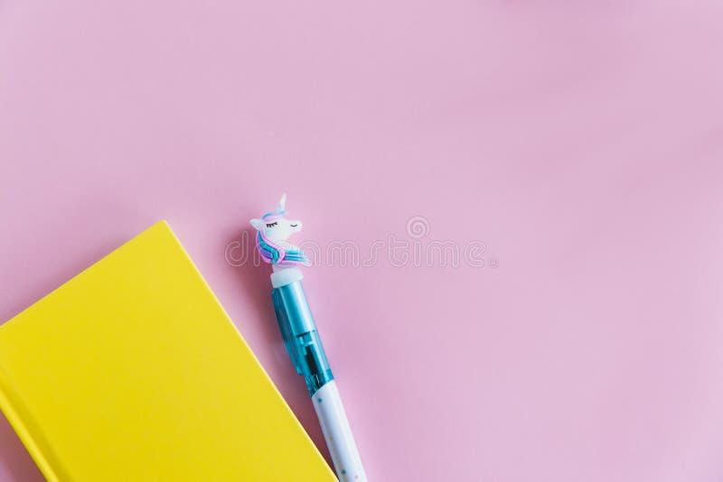 Carnet jaune pour des notes, stylo drôle de licorne sur le fond en pastel rose Configuration plate Vue supérieure Copiez l'espace photographie stock libre de droits