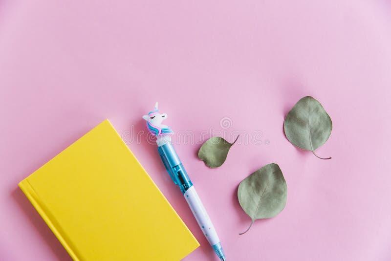 Carnet jaune pour les notes, le stylo drôle de licorne et les feuilles vertes d'eucalyptus sur le fond en pastel rose Configurati photographie stock libre de droits