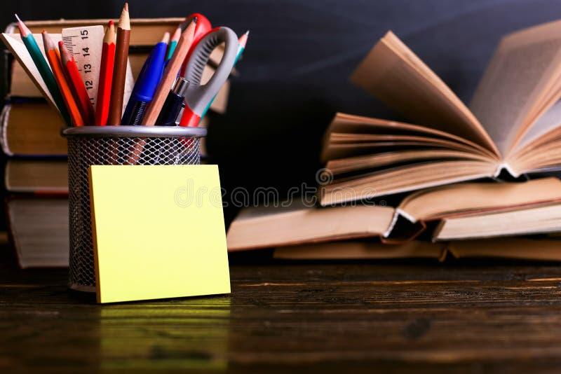 Carnet, livres ouverts et représenter des stylos sur une table en bois foncée sur le fond du panneau de craie Étude de la connais photo stock