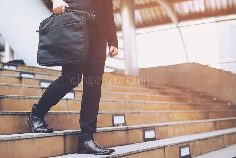 Carnet moderne d'ordinateur-valise de participation de main d'homme d'affaires près du travail étroitement vers le haut des jambe photos libres de droits