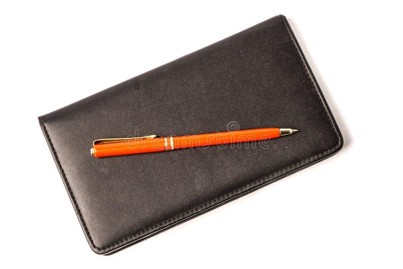 Carnet noir avec le stylo rouge d'isolement sur le fond blanc photo libre de droits