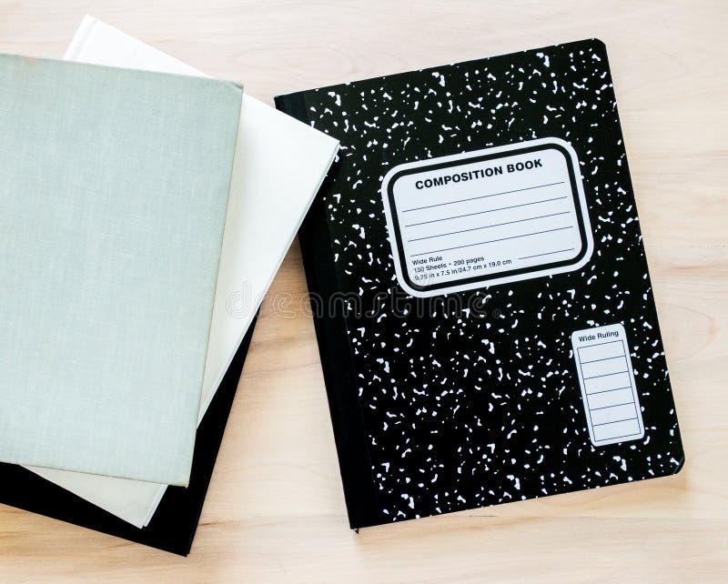 Carnet noir et blanc et livres bien usés sur un bureau en bois photographie stock