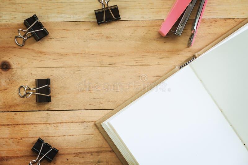 Carnet ouvert avec l'agrafe et l'agrafeuse de reliure sur le CCB en bois de table photo stock