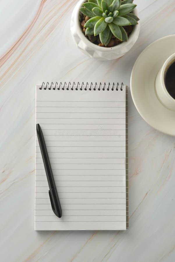 Carnet ouvert avec la tasse de caf?, usine succulente sur le bureau de marbre Lieu de travail, table de travail Vue sup?rieure photos stock