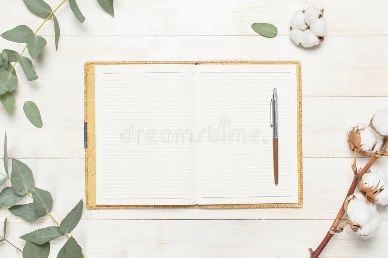 Carnet ouvert avec les pages vides, le stylo, la brindille d'eucalyptus et les fleurs de coton sur la configuration plate en bois images stock