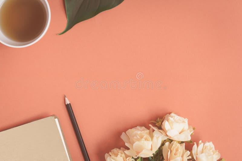 Carnet plat et rose de configuration placés sur un bureau rouge