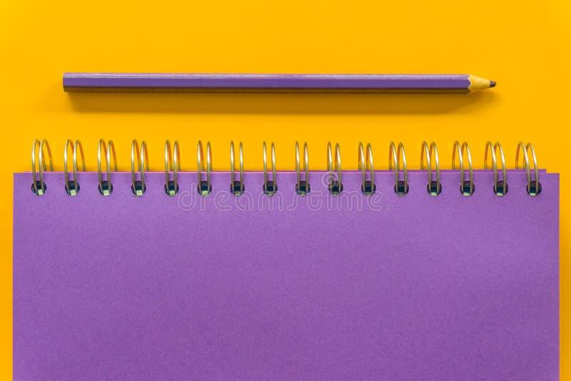 Carnet pourpre de stylo pourpre sur le fond jaune images libres de droits