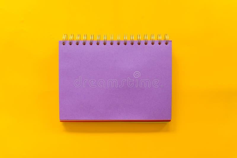 Carnet pourpre sur le fond jaune images libres de droits