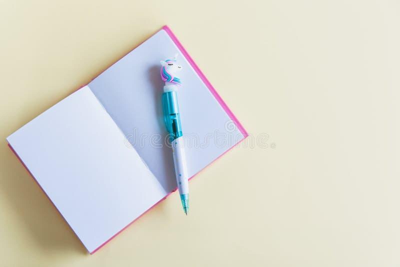 Carnet rose pour des notes, stylo drôle de licorne sur le fond en pastel jaune Configuration plate Vue supérieure Copiez l'espace photographie stock libre de droits