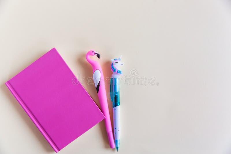 Carnet rose pour les notes, la licorne drôle et les stylos de flamant sur le fond en pastel jaune Configuration plate Vue supérie photo libre de droits