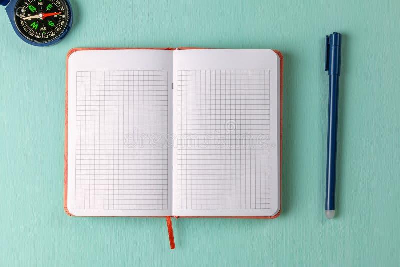 Carnet, stylo et boussole sur le fond vert photos libres de droits