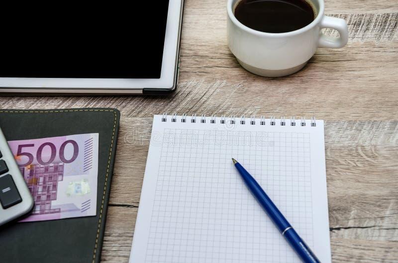 Carnet, stylo, tasse de café et argent sur le fond en bois photographie stock libre de droits