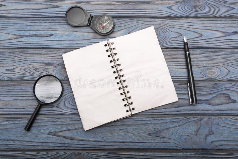 Carnet un ressort, stylo, loupe, boussole photo stock
