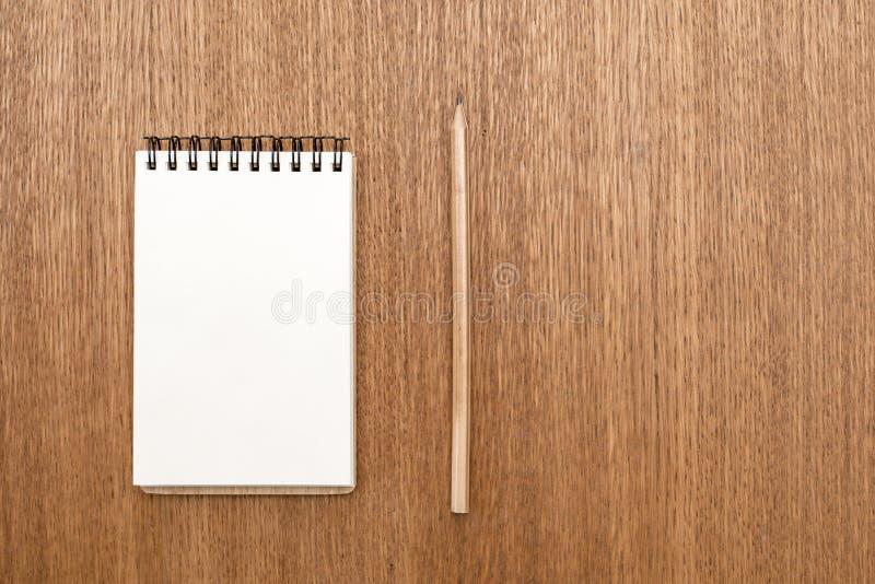 Carnet vide avec la spirale pour l'application des labels et du stylo sur le fond en bois photographie stock libre de droits