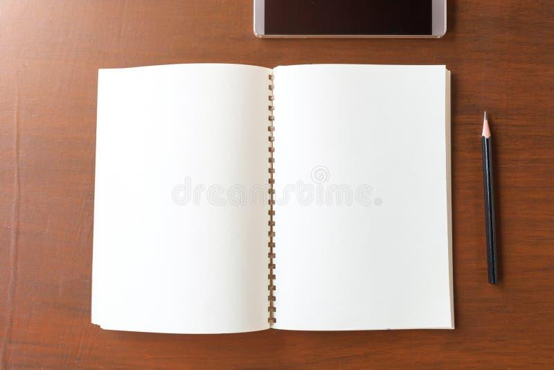 Carnet vide avec le crayon et le smartphone sur le backg en bois de table photographie stock