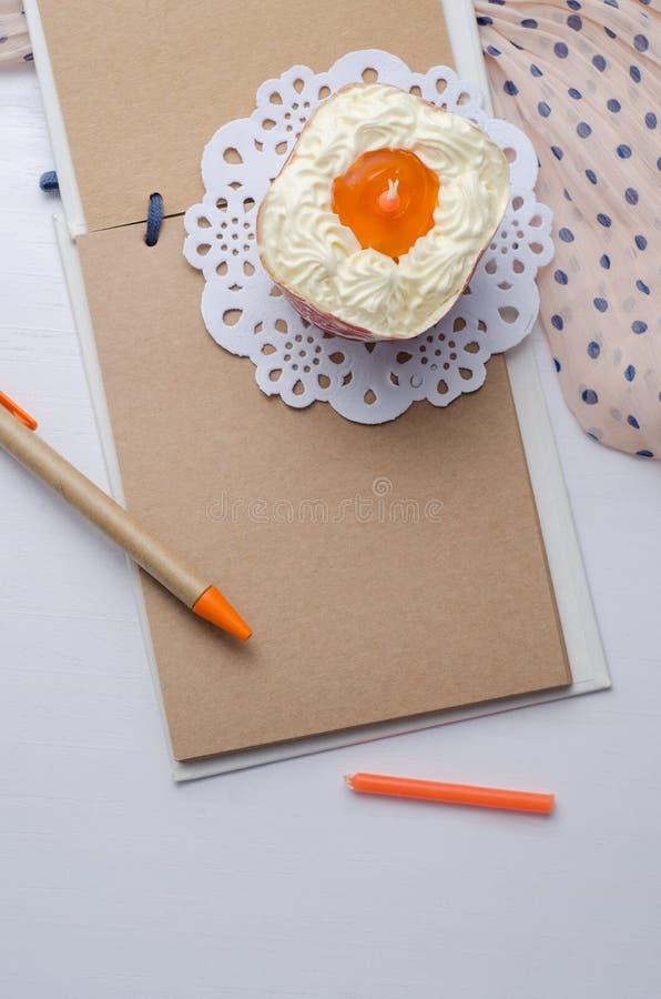 Carnet vide avec le stylo et petit gâteau sur la table en bois photos libres de droits