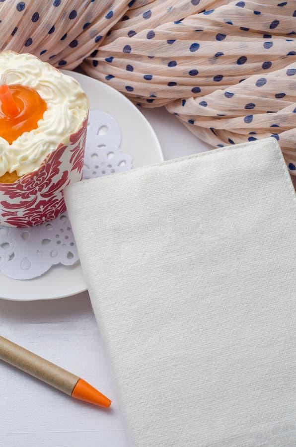 Carnet vide avec le stylo et petit gâteau sur la table en bois images libres de droits