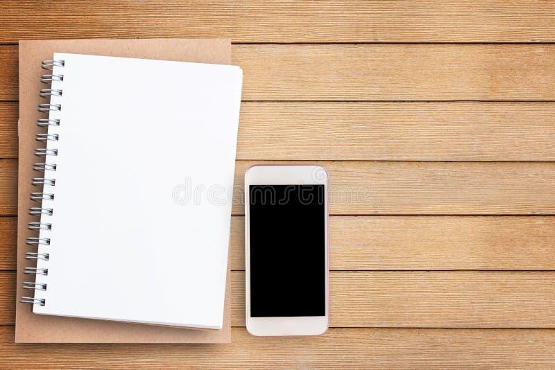 Carnet vide de papier blanc et téléphone intelligent sur la table en bois brune images stock