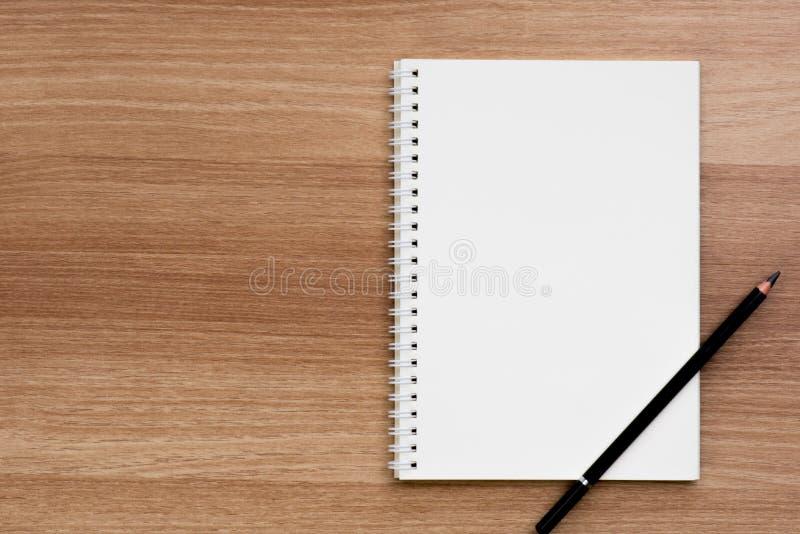 Carnet vide ouvert d'obligatoire en spirale d'anneau avec un crayon sur la surface en bois photos stock