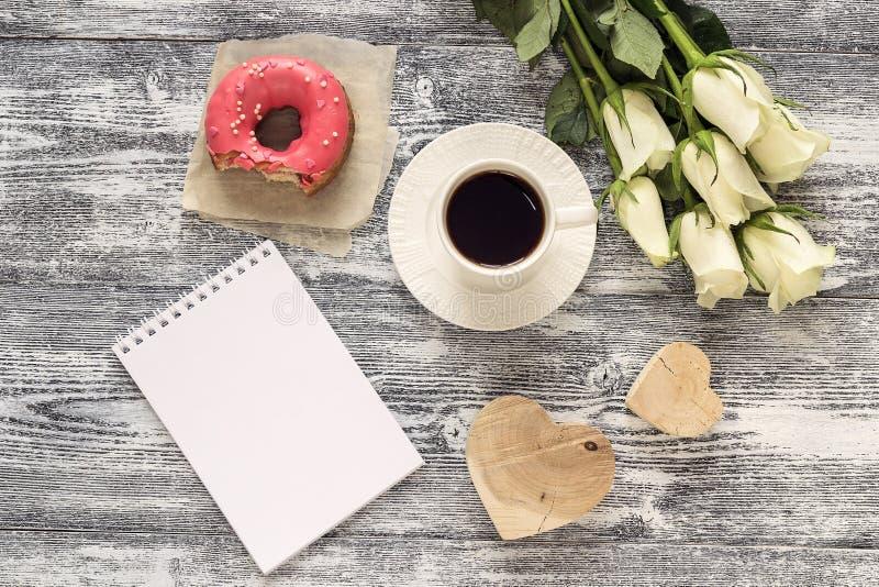 Carnet vide, tasse de café, beignet, coeurs et roses blanches dessus image stock