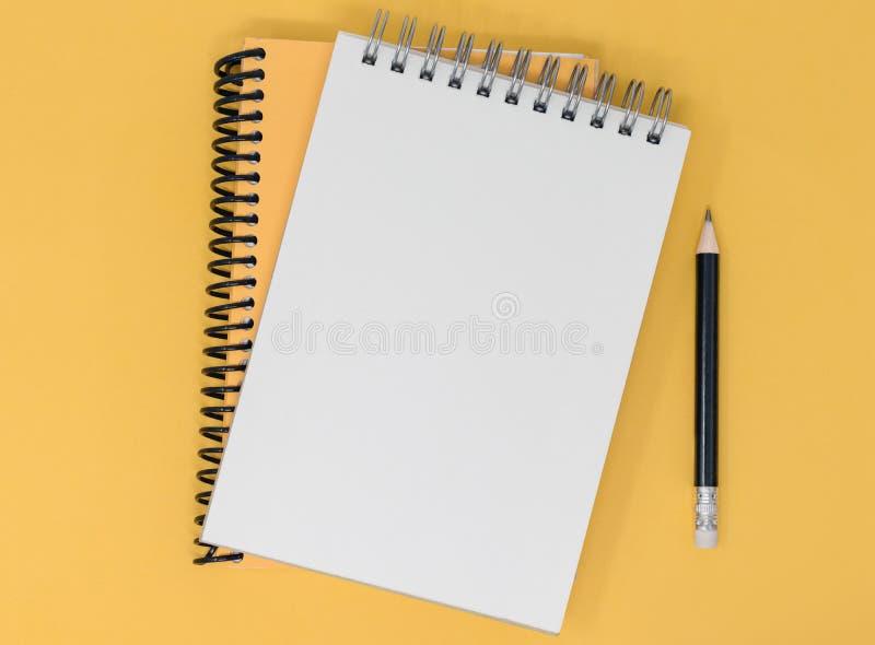 Carnets et crayon vides ouverts sur un fond jaune orange Vue sup?rieure avec l'espace de copie photo stock