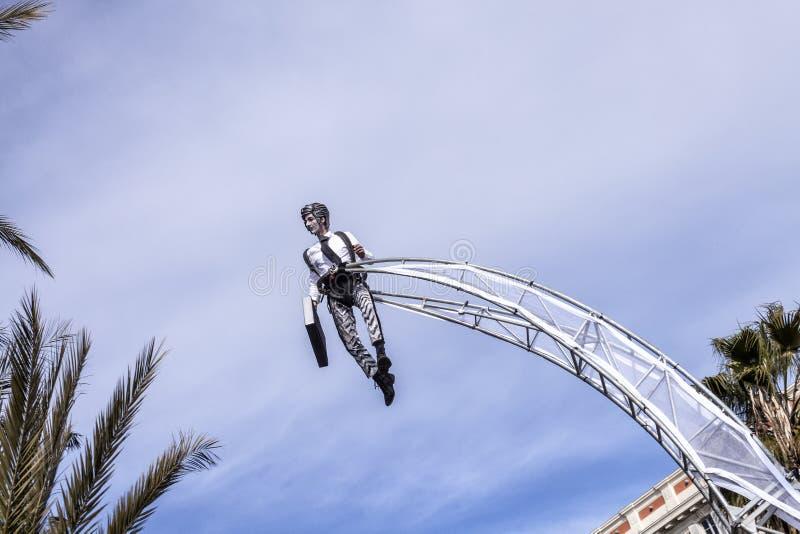 Carnevale famoso di Nizza, battaglia del ` dei fiori Nuvole su chiaro cielo blu con un acrobata nel vestito dell'uomo d'affari immagine stock libera da diritti