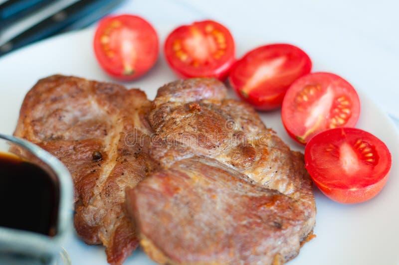 Carni di maiale o di manzo, salse, spezie e pomodoro, in lamiera grigia, salate di carne fritta, succhiate di carne fritta, su fo immagini stock
