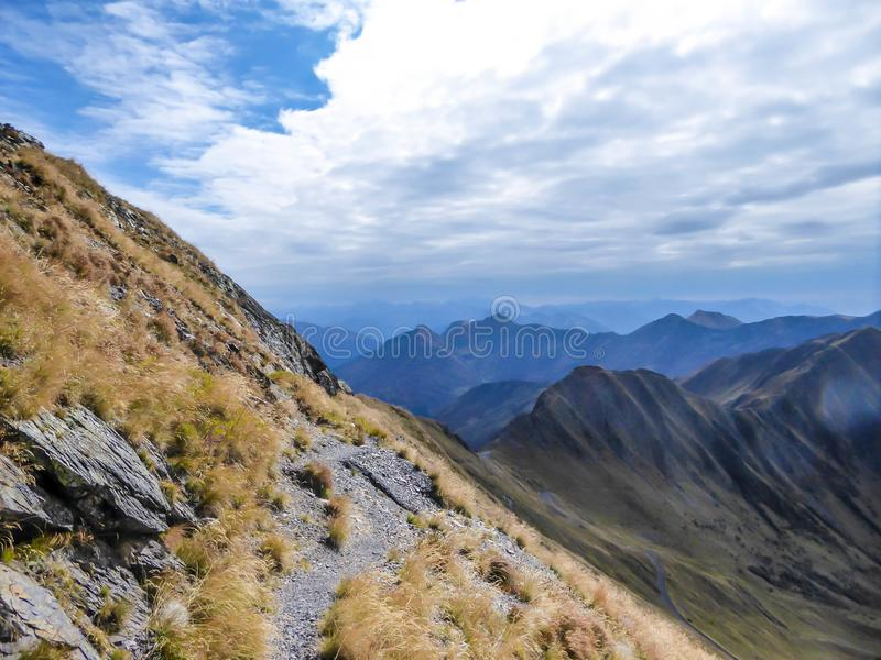 Carnic Alps - Autumn in the mountains, dried hiking trails. A stunning view on Alpine valley. The trail is overgrown with golden grass. Hiking trails in the high stock photography