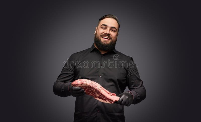 Carniceiro alegre com carne fresca fotografia de stock royalty free