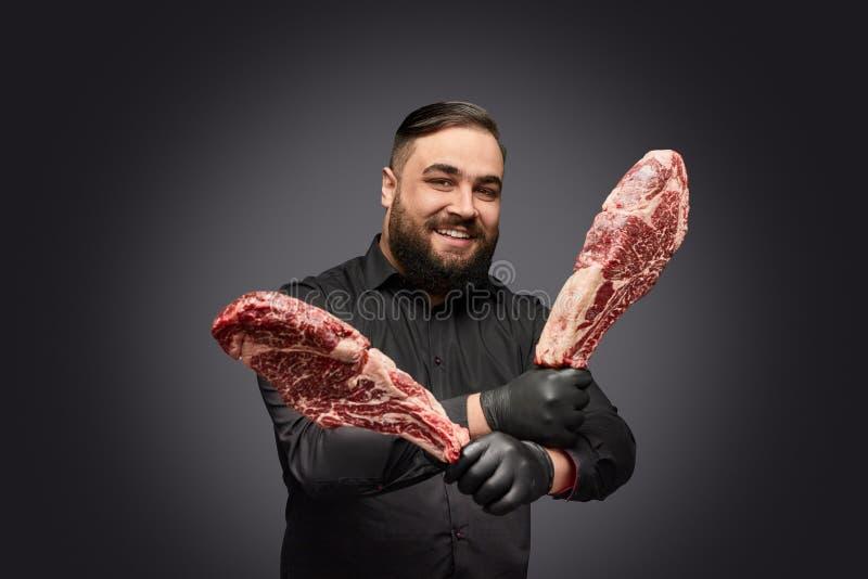 Carniceiro alegre que levanta com carne imagem de stock