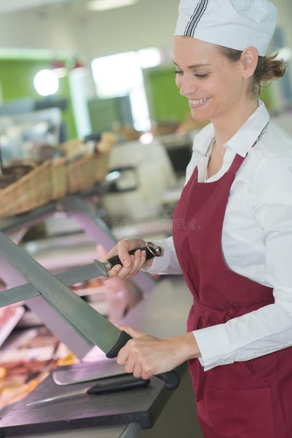 Carniceiro fêmea que sorri ao apontar a faca no açougue imagens de stock royalty free