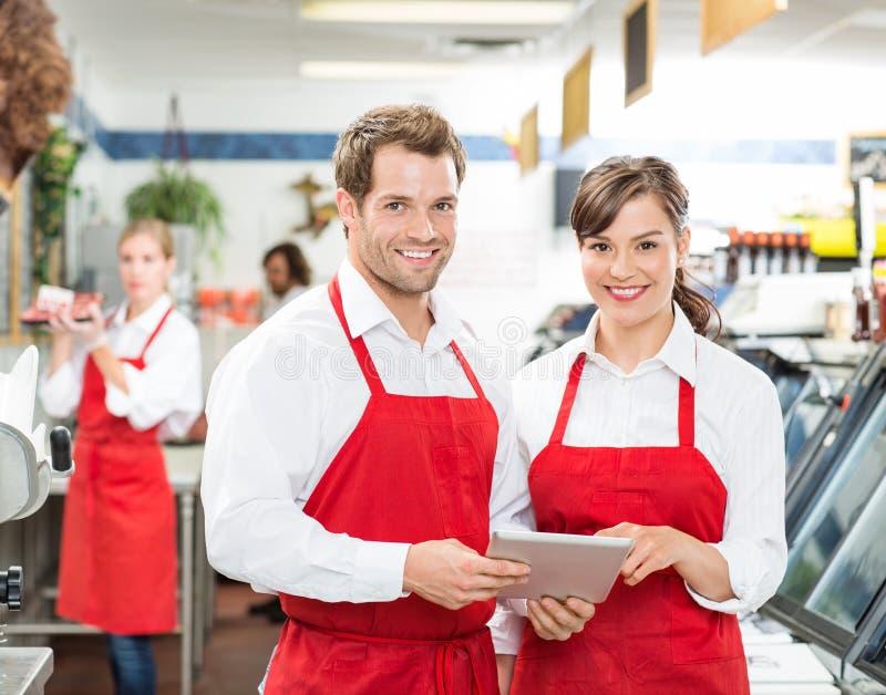 Carniceiros com a tabuleta de Digitas que está na loja imagem de stock
