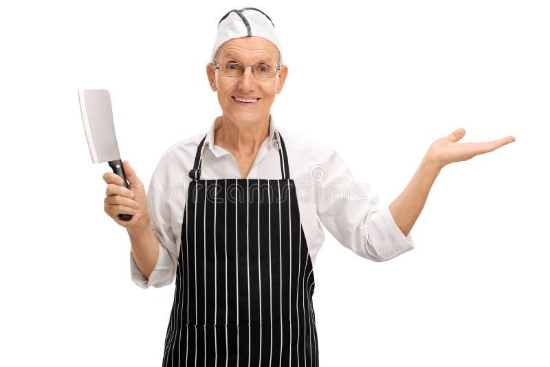 Carnicero maduro que celebra una cuchilla y gesticular fotos de archivo libres de regalías