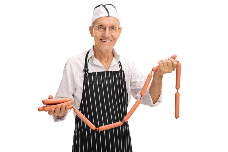 Carnicero mayor que sostiene las salchichas foto de archivo