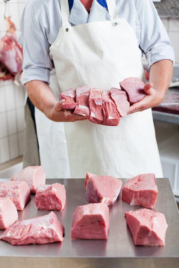 Carnicero que exhibe porciones de carne fotos de archivo