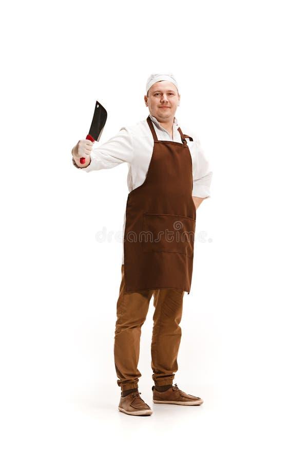 Carnicero sonriente que presenta con una cuchilla aislada en el fondo blanco fotografía de archivo libre de regalías