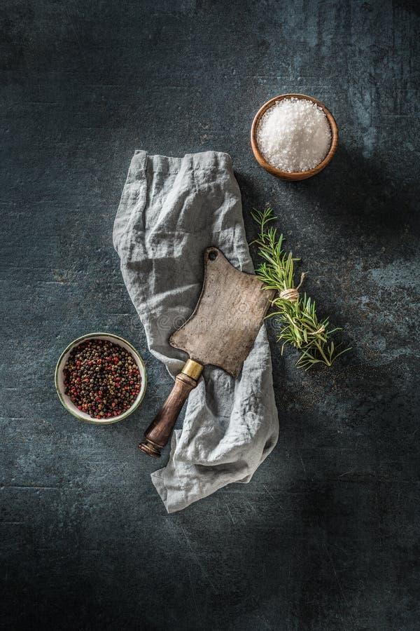 Carnicero viejo en una pizarra de hormigón oscuro con hierbas sal y pimienta foto de archivo