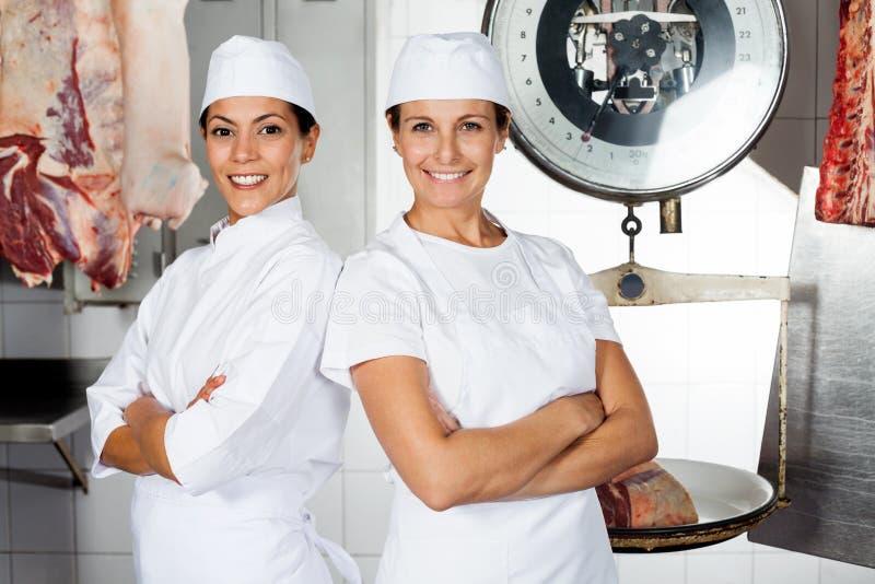 Carniceros de sexo femenino que colocan los brazos cruzados imagen de archivo