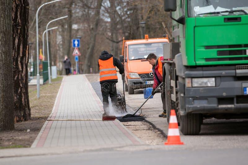 Carnikava, Letonia - 28 de abril de 2017: Trabajadores en una construcción de carreteras, una industria y un trabajo en equipo imagenes de archivo