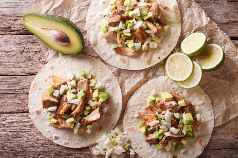 Carnitas Pork with onion and avocado on tortilla close-up. horizontal top view. Carnitas Pork with onion and avocado on tortilla close-up on the table royalty free stock photos