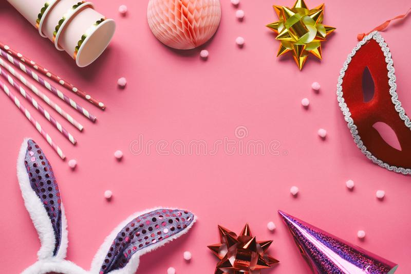 Carnival accessories set on pink background. Birthday or winter party props. Honeycomb balls, hair hoop in shape of rabbit ears,. Mask, paper cups and cocktail stock image