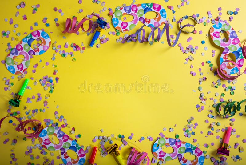Carnival or birthday party. Confetti and serpentines on bright yellow background. Top view, copy space stock images