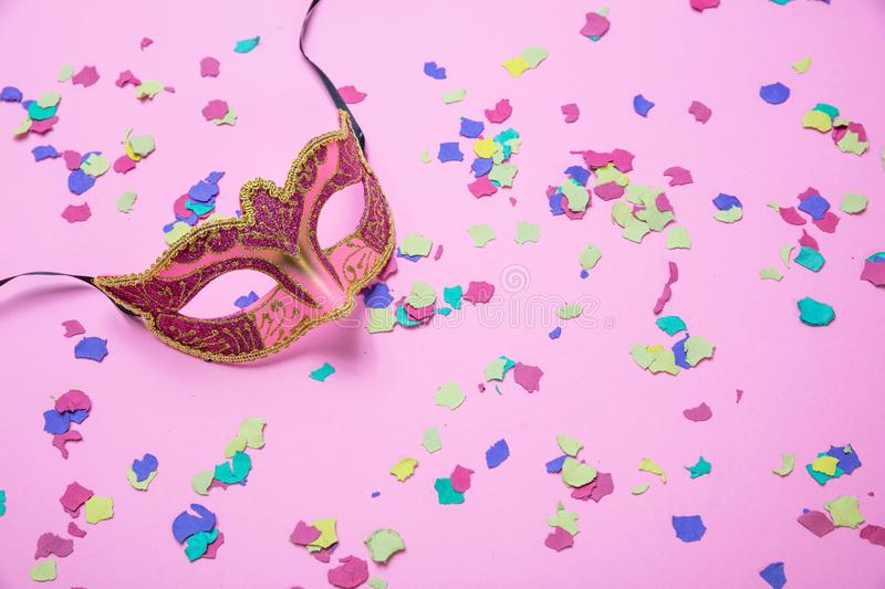 Carnival, birthday party. Female mask and colorful confetti on pink background stock photos