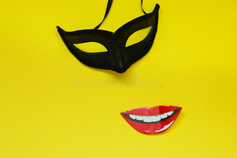 Carnival black mask and lip photo booth props on yellow background with copy space.  stock images