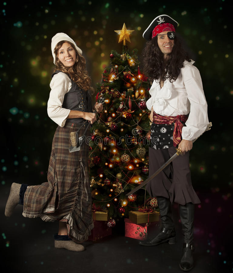 Carnival couple posing over Christmas tree stock photo