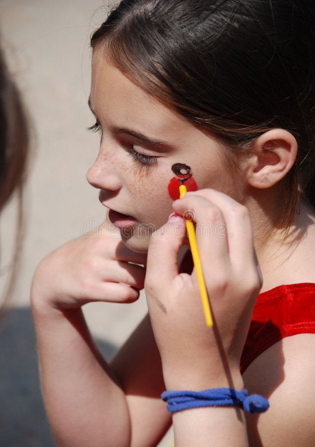 Carnival Face Painting on a Girl. Beautiful young girl having her face painted at a carnival stock images